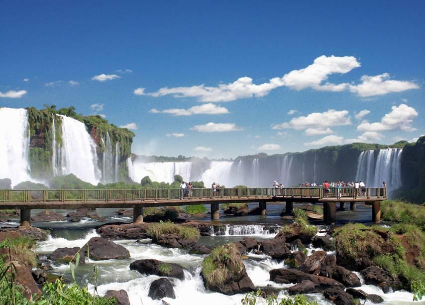 """Declarado pela UNESCO como Patrimônio Natural da Humanidade, o Parque Nacional do Iguaçu (PR), em <a href=""""http://viajeaqui.abril.com.br/cidades/br-pr-foz-do-iguacu"""" rel=""""Foz do Iguaçu"""" target=""""_self"""">Foz do Iguaçu</a>, é um camarote para o show das Cataratas, cenário impressionante formado por um cânion e 275 quedas – uma passarela de 1,2 km tem vista para a atração. A cada 15 minutos um ônibus sai do Centro de Visitantes e leva os turistas para outras partes do parque"""