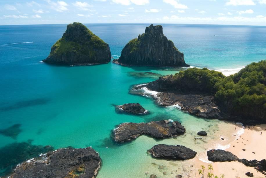 """<a href=""""http://viajeaqui.abril.com.br/estabelecimentos/br-pe-fernando-de-noronha-atracao-praia-da-baia-dos-porcos""""><b>Praia da Baía dos Porcos</b></a>A praia é pequena, com apenas 100 metros de extensão, mas veja a foto acima: ela justifica a fama, mas não diz tudo, pois a beleza dela está também nas piscinas naturais que se formam na maré baixa. Leve o snorkel e tome cuidado com as pedras escorregadias.A partir do mirante, faça uma foto clássica sua, com o Morro Dois Irmãos ao fundo. Acredite nos seus olhos e sorria, você está em Noronha."""