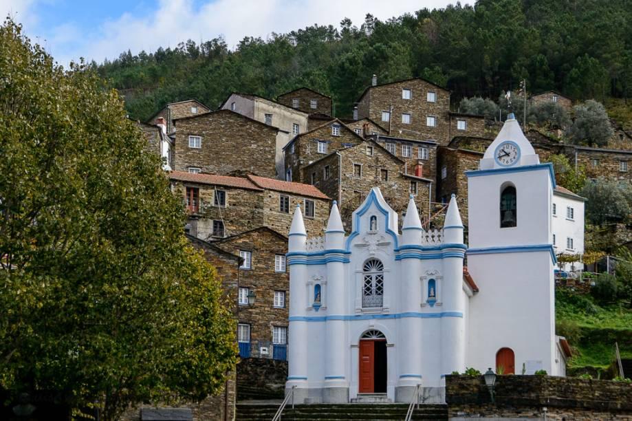 """Aos pés da Serra do Açor, o pequeno povoado de <strong>Piodão </strong>ergue-se com casinhas de xisto e uma igreja pintada de branco que se destaca na paisagem. Ela é chamada de """"Aldeia Presépio"""" e considerada uma das cidades mais típicas de Portugal"""