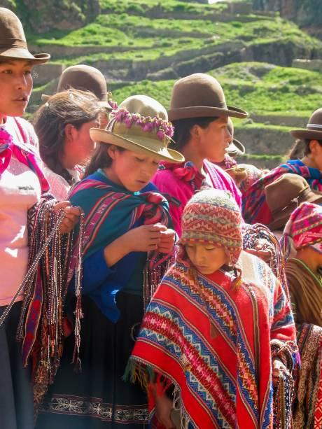 <strong>Peru: poncho</strong> Por conta de sua grande altitude, o Peru é um país ventoso. Para arrebatar o vento e o frio, a população peruana passou a utilizar o poncho, uma roupa feita de lã de lhama ou alpaca. O tecido é como um quadrado, que cai pelo ombro, e que conta uma abertura no centro. Costuma ser bem colorido, com temas e figuras geométricas e geralmente acompanha a utilização do chullo, uma espécie de gorro com um pompom no alto e duas partes que cobrem as orelhas