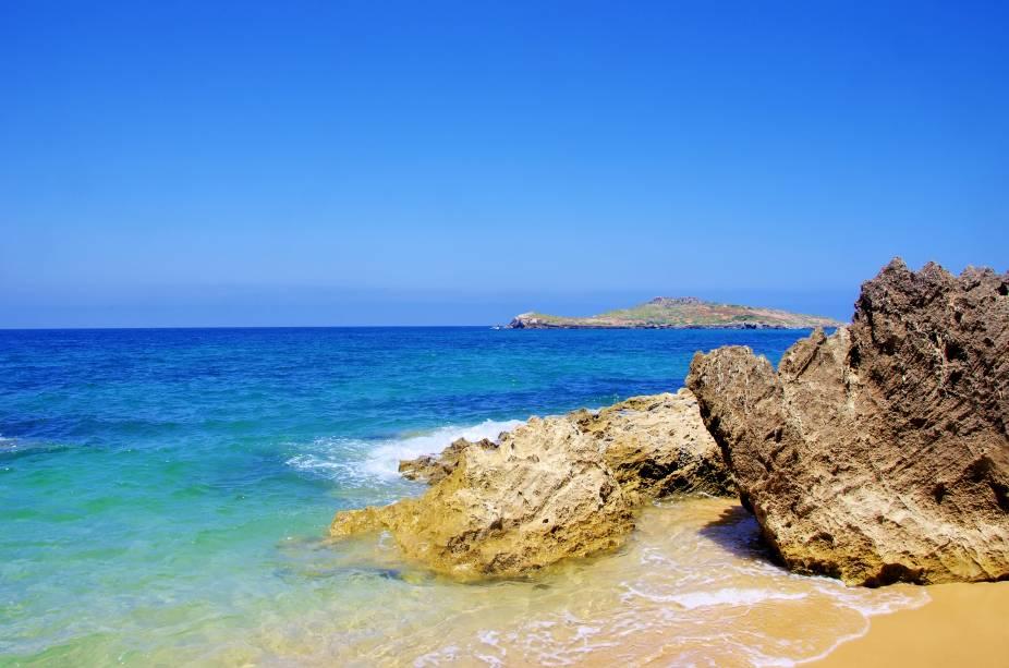 """Entre as várias praias de Porto Covo (e também de sua ilha, a do Pessegueiro), a escolhida para ser a queridinha dos turistas é a Praia Grande. Isso não é à toa, porque os tons de azul de suas águas, as formações rochosas e seu amplo espaço na areia, fazem dela dona de uma beleza excepcional.<a href=""""http://www.booking.com/city/pt/setubal.html?aid=332455&label=viagemabril-praiasportugal"""" target=""""_blank"""" rel=""""noopener noreferrer""""><em>Reserve o seu hotel em Setúbal através do Booking.com</em></a>"""