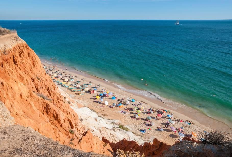 """Com uma faixa de areia bem larga e extensa (cerca de 5,5 quilômetros), essa grandiosa praia é conhecida por suas falésias de coloração alaranjada e esbranquiçada que, em alguns pontos, chegam a medir 40 metros de altura.<a href=""""http://www.booking.com/landmark/pt/falesia-beach.pt-pt.html?aid=332455&label=viagemabril-praiasportugal"""" target=""""_blank"""" rel=""""noopener noreferrer""""><em>Reserve o seu hotel perto da Praia da Falésia através do Booking.com</em></a>"""