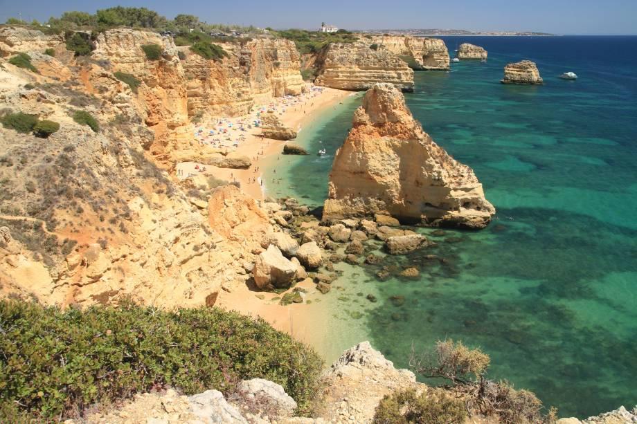 """Também atendendo pela alcunha de Praia Dourada, ela é considerada uma das 10 mais belas da <a href=""""http://viajeaqui.abril.com.br/continentes/europa"""" target=""""_blank"""" rel=""""noopener noreferrer"""">Europa</a> e, até mesmo, aparece em várias listas das 100 praias mais bonitas do mundo. É contornada por altas falésias alaranjadas que brilham à luz do sol e de onde é possível ter uma bela vista da região. As pedras ainda formam pequenos túneis entre as rochas que divertem as crianças. Além disso, ela ainda é muito bem preservada e natural, sem muitas intervenções humanas.<a href=""""http://www.booking.com/landmark/pt/praia-da-marinha.html?aid=332455&label=viagemabril-praiasportugal"""" target=""""_blank"""" rel=""""noopener noreferrer""""><em>Reserve o seu hotel na Praia da Marinha através do Booking.com</em></a>"""