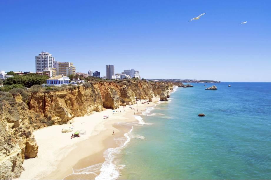 """Ser uma das mais belas praias de <a href=""""http://viajeaqui.abril.com.br/paises/portugal"""" target=""""_blank"""" rel=""""noopener noreferrer"""">Portugal</a> tem seus preços: o local, durante o verão, está sempre cheio de turistas, mesmo com sua extensa faixa de areia, de 1,5 quilômetro. O lado bom é que, em seu entorno, existem várias e ótimas opções de bares e restaurantes.<a href=""""http://www.booking.com/district/pt/portimao/praia-da-rocha.html?aid=332455&label=viagemabril-praiasportugal"""" target=""""_blank"""" rel=""""noopener noreferrer""""><em>Reserve o seu hotel em através do Booking.com</em></a>"""