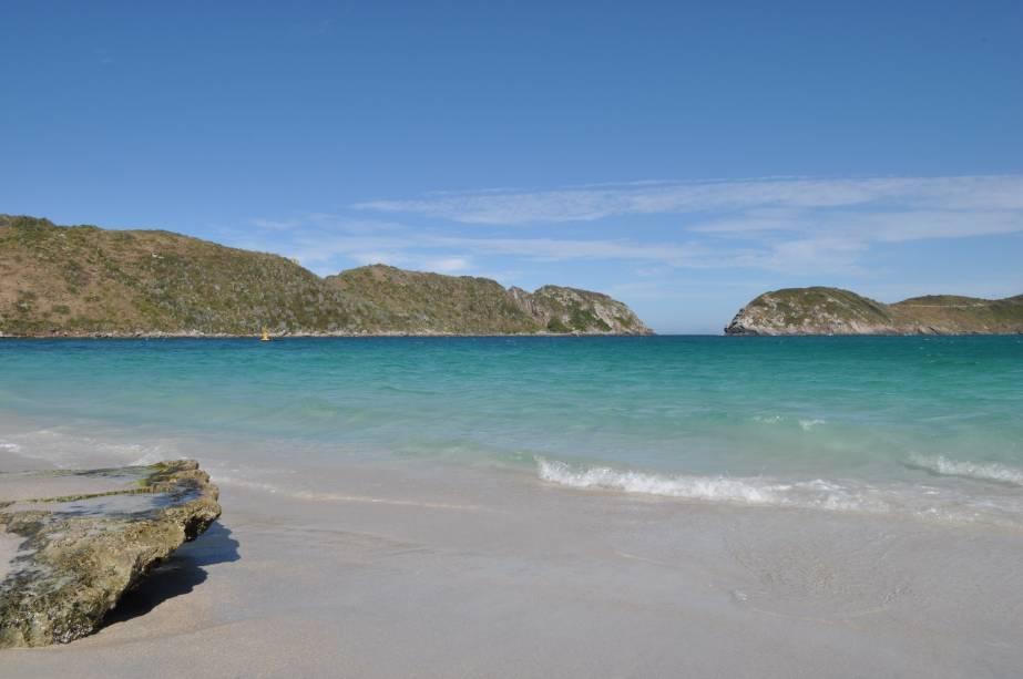 """<strong>LOGO ALI: </strong><strong>4. <a href=""""http://viajeaqui.abril.com.br/cidades/br-rj-arraial-do-cabo"""" rel=""""Arraial do Cabo"""" target=""""_blank"""">Arraial do Cabo</a></strong>A pouco mais de 35 quilômetros de distância, Arraial do Cabo não tem a badalação ou o charme dos lugarzinhos de Búzios. Ainda assim, vale reservar um dia e esticar o passeio até aqui por dois motivos: as praias do <strong>Farol</strong> <em>(foto)</em> e do Pontal do Atalaia. A primeira fica numa ilha com entrada controlada pela Marinha, onde a permanência máxima é de 1 hora; barcos levam até o cenário paradisíaco de mar transparente e dunas de areia branca e fininha. A segunda, no Pontal do Atalaia, fica no continente e é composta por duas enseadas esverdeadas que se unem na maré baixa (o acesso é por uma escadaria de madeira a partir do Morro do Atalaia). Aqui também a areia é branca e a água, cristalina."""