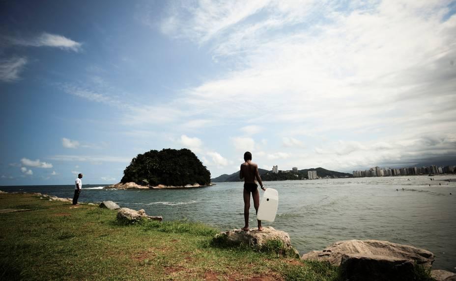 Menino observa as ondas com sua prancha de bodyboard na Praia de José Menino