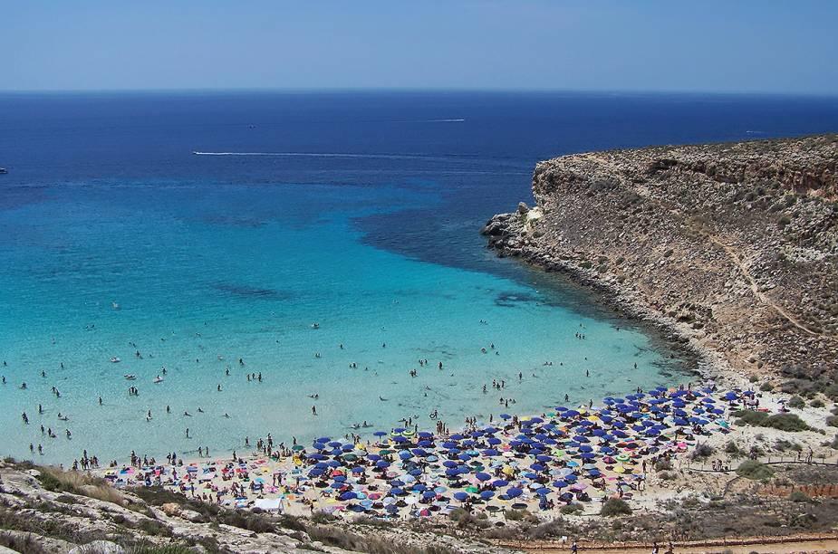 "<strong>Rabbit-Beach</strong>A Rabbit Beach pertence à Ilha de Lampedusa, na costa sul da Sicília. O acesso à praia só é feito por barco. Essa é uma das poucas praias no mediterrâneo onde tartatugas colocam seus ovos e os turistas frequentam.Em 2013, ela levou o título de melhor do mundo!<em><a href=""https://www.booking.com/searchresults.en-gb.html?aid=332455&lang=en-gb&sid=eedbe6de09e709d664615ac6f1b39a5d&sb=1&src=searchresults&src_elem=sb&error_url=https%3A%2F%2Fwww.booking.com%2Fsearchresults.en-gb.html%3Faid%3D332455%3Bsid%3Deedbe6de09e709d664615ac6f1b39a5d%3Bclass_interval%3D1%3Bdest_id%3D-111354%3Bdest_type%3Dcity%3Bdtdisc%3D0%3Bfrom_sf%3D1%3Bgroup_adults%3D2%3Bgroup_children%3D0%3Binac%3D0%3Bindex_postcard%3D0%3Blabel_click%3Dundef%3Bno_rooms%3D1%3Boffset%3D0%3Bpostcard%3D0%3Braw_dest_type%3Dcity%3Broom1%3DA%252CA%3Bsb_price_type%3Dtotal%3Bsearch_selected%3D1%3Bsrc%3Dindex%3Bsrc_elem%3Dsb%3Bss%3DBaunei%252C%2520%25E2%2580%258BSardinia%252C%2520%25E2%2580%258BItaly%3Bss_all%3D0%3Bss_raw%3DBauney%3Bssb%3Dempty%3Bsshis%3D0%26%3B&ss=Lampedusa%2C+%E2%80%8BSicily%2C+%E2%80%8BItaly&ssne=Baunei&ssne_untouched=Baunei&city=-111354&checkin_monthday=&checkin_month=&checkin_year=&checkout_monthday=&checkout_month=&checkout_year=&no_rooms=1&group_adults=2&group_children=0&highlighted_hotels=&from_sf=1&ss_raw=%C2%A0Lampedusa&ac_position=0&ac_langcode=en&dest_id=-119645&dest_type=city&place_id_lat=35.50353&place_id_lon=12.60669&search_pageview_id=0419903e64f60084&search_selected=true&search_pageview_id=0419903e64f60084&ac_suggestion_list_length=5&ac_suggestion_theme_list_length=0"" target=""_blank"" rel=""noopener"">Busque hospedagens emLampedusa no Booking.com</a></em>"