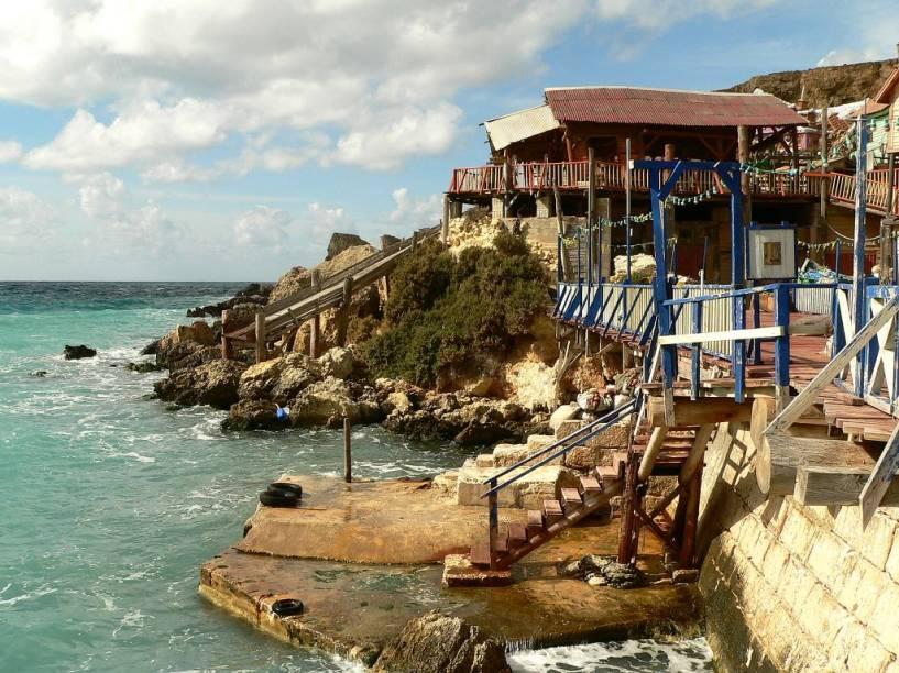As águas esverdeadas do Mediterrâneo emolduram o cenário com casas de madeira coloridas