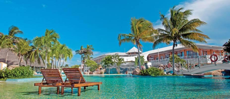 """<strong><a href=""""http://www.royaltonresorts.com/en/royalton-hicacos.aspx"""" rel=""""Royalton Hicacos Varadero Resort & Spa"""" target=""""_blank"""">Royalton Hicacos Varadero Resort & Spa</a> - <a href=""""http://viajeaqui.abril.com.br/paises/cuba"""" rel=""""Cuba"""" target=""""_blank"""">Cuba</a></strong>Localizado na península de Hicacos em Cuba, esse resort à beira da praia é exclusivo para adultos. Sua piscina principal é enorme, com pontes, cachoeiras e um bar no meio das águas. O resort tem também outras duas piscinas, spa e salão de beleza, tudo incluído na diária. Atividades aquáticas como vela, windsurf, snorkel e mergulho (para quem já tem certificado) estão à disposição dos hóspedes. Seis bares fornecem drinks 24h e cinco restaurantes servem pratos de diferentes escolas gastronômicas. A praia em frente é paradisíaca, com ampla faixa de areia branca e fina, onde você também pode pedir seus drinks e comidinhas"""