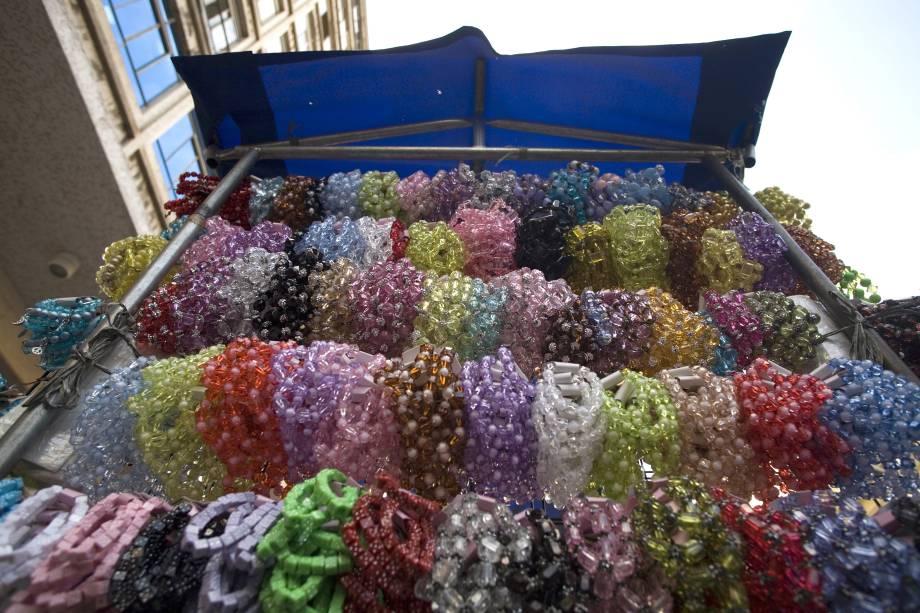 Barraca vende pulseiras plásticas na calçada da Rua 25 de Março, São Paulo