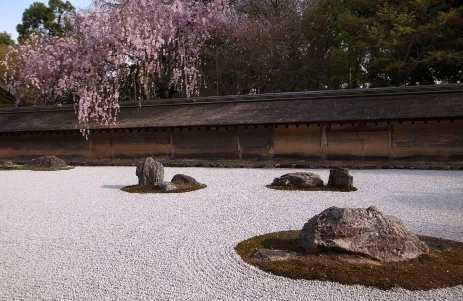 <strong>Ryoan-ji </strong> Localizado na parte nordeste da cidade, o templo também é Patrimônio Mundial da Humanidade pela UNESCO e tem destaque para seu jardim de pedras, o mais famoso do Japão. Apesar de sua história e significado não serem claros, o jardim é considerado uma obra prima desta forma de arte japonesa, que vem do zen budismo: as pedras são cuidadosamente arranjadas em um terreno forrado de cascalho com linhas desenhadas, criando um design que deve reproduzir a essência da natureza e ajudar na meditação zazen. Neste jardim, 15 pedras foram posicionadas de tal maneira que não importa a partir de que ponto se olha, somente 14 serão visíveis. Reza a lenda que só é possível avistar todas as pedras ao mesmo tempo quando o praticante do zen budismo atingir o nirvana.