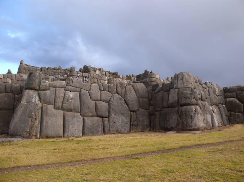"""<strong>Sacsayhuamnán (continuação)</strong>        Pedras pesando dezenas de toneladas, perfeitamente encaixadas umas nas outras, formam as muralhas de <a href=""""http://viajeaqui.abril.com.br/estabelecimentos/peru-cusco-atracao-complexo-arqueologico-de-sacsayhuaman"""">Sacsayhuamán</a>. A técnica de manuseio destes gigantes é tema de diversas teorias e muitas especulações"""