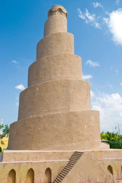 """Inaugurada em 851, essa mesquita foi a maior de seu tempo até que foi destruída em 1278. O impressionante minarete Malwiya, felizmente, persiste na paisagem plana de Samarra – pelo menos por enquanto. Com 52 metros de altura e 33 metros de diâmetro, sua forma é inspirada nos zuggurats da Mesopotâmia. O minarete é feito de arenito amarelo e é possível chegar até o topo pela sua rampa em espiral. Seu nome árabe, Malwiya, se traduz como """"retorcido"""" ou """"concha de caracol"""". O topo do minarete foi danificado por uma bomba em 2005. De acordo com a polícia iraquiana, insurgentes explodiram essa área porque ela estava sendo usada como ponto de observação de tropas estadunidenses – os soldados haviam evacuado o local um mês antes do ataque. Está na lista da UNESCO de Patrimônios Ameaçados da Humanidade"""