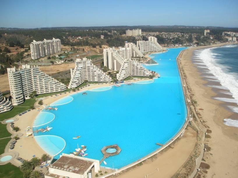 """O complexo, cheio de propriedades particulares, oferece apartamentos para serem alugados. A piscina gigantesca, uma espécie de ilha artificial tem algumas áreas permitidas para banho. A visão que se tem do mar compensa a viagem <em><a href=""""http://www.booking.com/hotel/cl/algarrobopropiedades-vista-bahia.pt-br.html?aid=332455&label=viagemabril-as-piscinas-mais-incriveis-do-mundo"""" target=""""_blank"""">Veja os preços do San Alfonso del Mar no Booking.com</a></em>"""