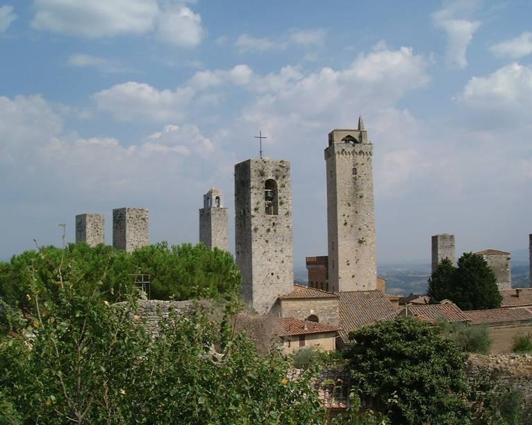 """<strong>SAN GIMIGNIANO</strong> (a 20 km de Greve in Chianti)    A próxima parada é em <a href=""""http://viajeaqui.abril.com.br/cidades/italia-san-gimignano"""" rel="""" San Gimigniano"""" target=""""_blank""""><strong>San Gimigniano</strong></a>. A cidade das torres tem origens na antiga civilização etrusca. Alcançou um grande desenvolvimento durante a Idade Média, o que explica a grande quantidade de obras de arte que adornavam suas igrejas e conventos.    Durante esse período, as famílias patrícias que dominavam a região construíram as 74 torres que serviam para demonstrar o grau de poder de cada uma delas. Hoje restam apenas 14.    Aqui é o berço e a terra de outro famoso vinho italiano: <em>Vernaccia di San Gimigniano</em>. A produção é feita dentro dos limites de <strong>San Gimigniano</strong> e é administrada pelo <em>Consorzio della Denominazione di San Gimigniano </em>que congrega as produtoras locais.    A uva branca <em>Vernaccia</em> é encontrada em várias regiões da Itália, mas foi na Toscana onde encontrou as condições ideais para o cultivo: o clima mediterrâneo, o solo calcário e altitudes que não ultrapassam os 400 metros. Manter o respeito à tradição e possuir um dos vinhedos autóctones mais antigos da Itália, que se renovou com as modernas tecnologias sem perder a sua identidade, fez do <em>Vernaccia</em> um vinho branco único no mundo.    As vinícolas do consórcio produzem três tipos de vinho: <em>Vernaccia di San Gimignano D.O.C.G</em>., <em>San Gimignano D.O.</em>C. Rosso e <em>San Gimigniano</em> <em>D.O.C. Vin Santo</em>, nos quais a porcentagem da uva <em>vernaccia</em> é, no mínimo, 90%. O programa aqui é conhecer as vinícolas do Consórcio, para degustar e comprar os vinhos locais. Agende a sua visita acessando o <a href=""""http://www.vernaccia.it/aziende.aspx"""" rel=""""site da vinícola"""" target=""""_blank"""">site da vinícola</a>.    Conheça também Il Duomo ou Chiesa Collegiata, consagrada no ano de 1148, onde se conservam belos afrescos na Piazza del Duomo, o Palazzo """