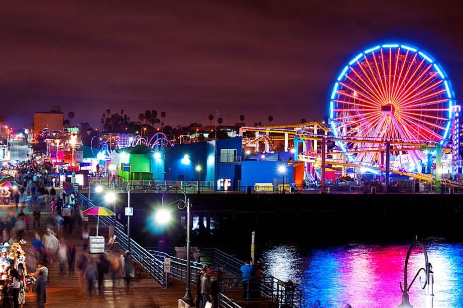 """O Píer Santa Monica é considerado o verdadeiro final da famosa Rota 66, o que já é legal por si só, mas ele vai além. O local é prato cheio para quem procura diversão: são 12 brinquedos, 18 barraquinhas de jogos e praça de alimentação à beira do oceano. A coloridíssima roda-gigante tem 26 metros de altura, 20 gôndolas e 160 mil lâmpadas de LED de enfeite.É um dos locais mais românticos da região de <a href=""""http://viajeaqui.abril.com.br/cidades/estados-unidos-los-angeles"""" target=""""_blank"""">Los Angeles</a> e a vista vale a pena – do alto dá para ver todo o litoral, a Ilha Catalina, Malibu e a Península Palos Verdes. E um ponto muito positivo: esta roda é a única do mundo a funcionar com energia solar, amiga do meio ambiente!"""