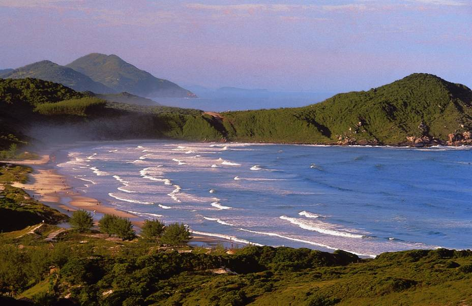 """<strong>1. Praia do Rosa, Imbituba</strong> Também há trilhas pela Mata Atlântica que levam direto à areia. Sem estrutura de quiosques ou barracas, a praia impressiona pelo verde e pelos dois costões de pedra. Ao centro, a Lagoa do Meio reúne famílias em busca das águas calmas de temperatura mais amena. Jovens e surfistas concentram-se nos extremos. <a href=""""https://www.booking.com/searchresults.pt-br.html?aid=332455&lang=pt-br&sid=eedbe6de09e709d664615ac6f1b39a5d&sb=1&src=index&src_elem=sb&error_url=https%3A%2F%2Fwww.booking.com%2Findex.pt-br.html%3Faid%3D332455%3Bsid%3Deedbe6de09e709d664615ac6f1b39a5d%3Bsb_price_type%3Dtotal%26%3B&ss=Praia+do+Rosa%2C+Santa+Catarina%2C+Brasil&checkin_monthday=&checkin_month=&checkin_year=&checkout_monthday=&checkout_month=&checkout_year=&no_rooms=1&group_adults=2&group_children=0&from_sf=1&ss_raw=Praia+do+Rosa&ac_position=0&ac_langcode=xb&dest_id=900048708&dest_type=city&search_pageview_id=2c456d55ff360190&search_selected=true&search_pageview_id=2c456d55ff360190&ac_suggestion_list_length=5&ac_suggestion_theme_list_length=0"""" target=""""_blank"""" rel=""""noopener""""><em>Busque hospedagens na Praia do Rosa no Booking.com</em></a>"""