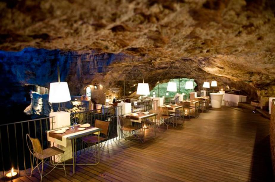 """Ao sul da cidade de <a href=""""http://viajeaqui.abril.com.br/cidades/italia-bari"""" target=""""_blank"""" rel=""""noopener"""">Bari</a>, o restaurante <a href=""""https://www.grottapalazzese.it/ristorante/"""" target=""""_blank"""" rel=""""noopener"""">Grotta Palazzese</a> fica dentro de uma caverna natural. A 20 metros acima do nível do mar, tem uma vista incrível para o Mar Adriático. Fazem parte do menu pratos típicos do mediterrâneo e, é claro, bons vinhos italianos"""