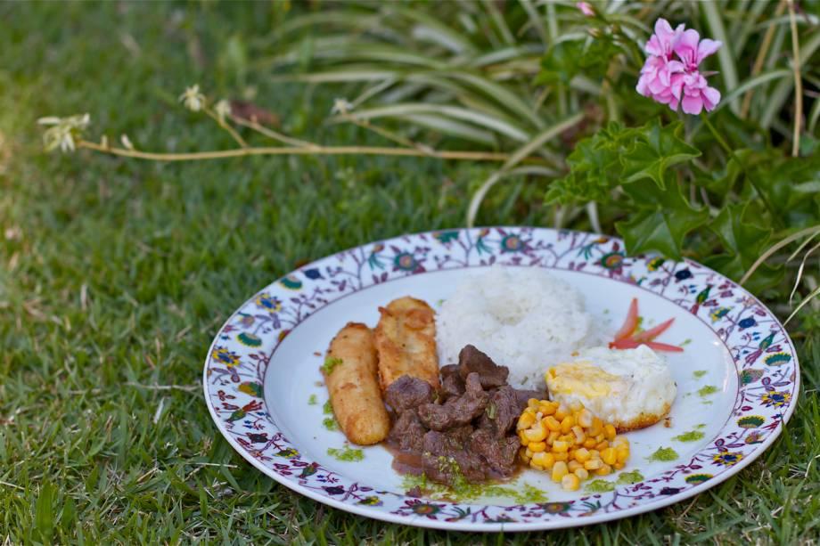 """O<a href=""""http://viajeaqui.abril.com.br/estabelecimentos/br-rj-petropolis-hospedagem-solar-fazenda-do-cedro"""" rel=""""Solar Fazenda do Cedro"""">Solar Fazenda do Cedro</a> serve picadinho de carne servido com arroz branco, farofa, milho verde, ovo estrelado e banana frita"""