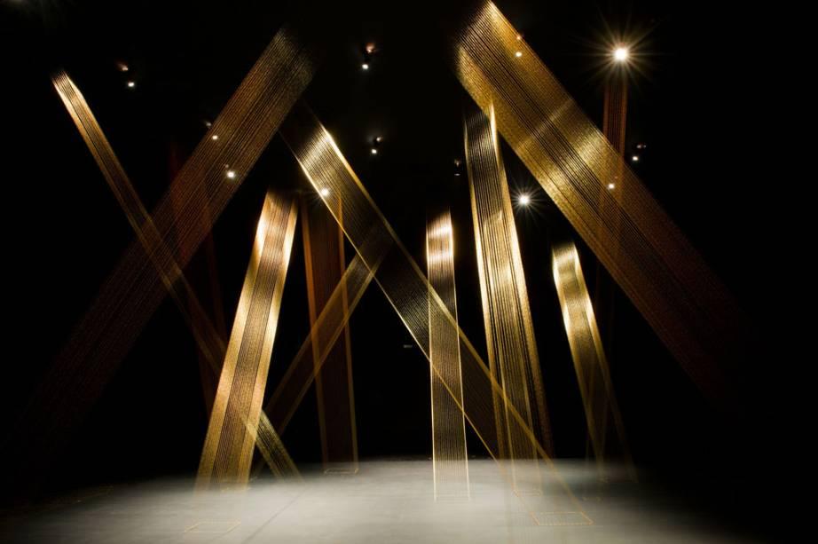 Fios dourados finos e iluminação especial criam um efeito diferente a cada ângulo na obra T-teia, de Lygia Pape.
