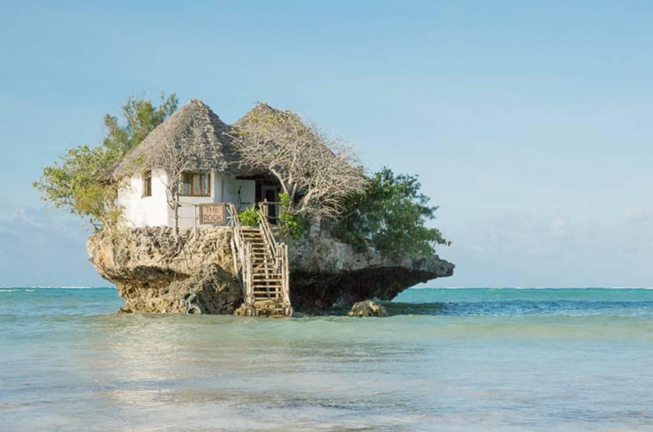 """O badalado <a href=""""https://www.therockrestaurantzanzibar.com/"""" target=""""_blank"""" rel=""""noopener"""">The Rock Restaurant</a> fica sobre uma rocha no meio do mar. Para chegar até lá, é possível ir andando quando a maré está baixa ou de barco, quando a água sobe. Com apenas doze mesas, e ao ar livre, a especialidade da casa são frutos do mar. O local é um dos ícones da ilha e costumava servir como abrigo para pescadores. Também já foi locação para importantes ensaios de moda"""