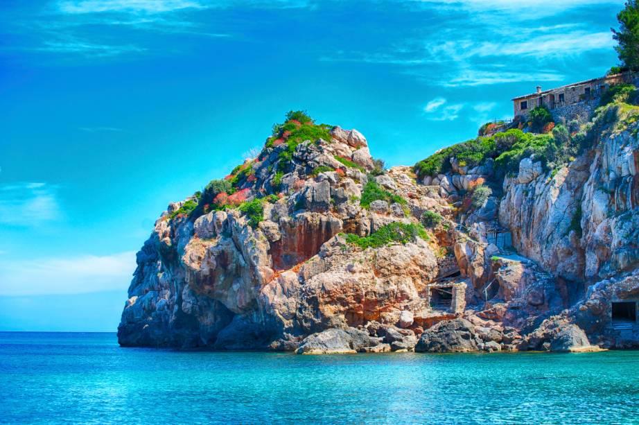 """<strong>Cala de Deia, Maiorca, <a href=""""http://viajeaqui.abril.com.br/paises/espanha"""" rel=""""Espanha"""" target=""""_self"""">Espanha</a></strong>                    Pequena, de águas cristalinas e com piscinas naturais em meio às rochas, a praia é a eleita de muitos artistas graças à sua privacidade. Altos penhascos cercam a paisagem, com áreas que reservam bons restaurantes. Vale a pena esticar a viagem até o vilarejo de Deia, com uma atmosfera boêmia que atrai um público jovem e diversificado                    <em><a href=""""http://www.booking.com/region/es/mallorca.pt-br.html?sid=5b28d827ef00573fdd3b49a282e323ef;dcid=4aid=332455&label=viagemabril-as-mais-belas-praias-do-mediterraneo"""" rel=""""Veja preços de hotéis em Maiorca no Booking.com"""" target=""""_blank"""">Veja preços de hotéis em Maiorca no Booking.com</a></em>"""