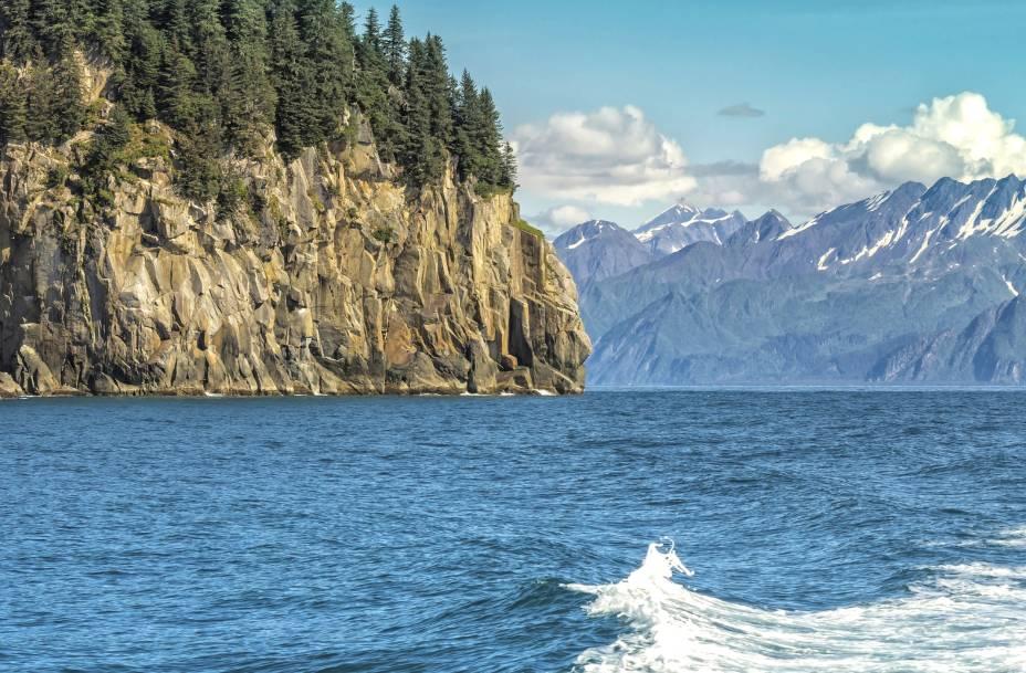 """A <strong>Ressurection Bay</strong> ofecere uma visão espetacular das montanhas. O passeio por suas águas, feito a partir do <strong>Porto de Seward</strong>, inclui vislumbres da atividade selvagem de espécies marinhas, tais como baleias e leões-marinhos    <em><a href=""""http://www.booking.com/city/us/seward.pt-br.html?sid=5b28d827ef00573fdd3b49a282e323ef;dcid=1?aid=332455&label=viagemabril-paisagens-do-alasca"""" rel=""""Veja preços de hotéis em Seward no Booking.com"""" target=""""_blank"""">Veja preços de hotéis em Seward no Booking.com</a></em>"""