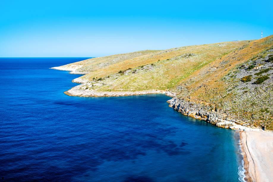 """<strong>Dhermi Beach, Vlorë, Albânia</strong>        O cenário é simplesmente surreal e impressiona os turistas. A água, de um azul impressionante, é extremamente convidativa a mergulhos. Ao longo da orla, é possível encontrar lugares bacanas pra fazer um lanche        <em><a href=""""http://www.booking.com/city/al/vlore.pt-br.html?sid=5b28d827ef00573fdd3b49a282e323ef;dcid=4aid=332455&label=viagemabril-as-mais-belas-praias-do-mediterraneo"""" rel=""""Veja preços de hotéis em Vlorë no Booking.com"""" target=""""_blank"""">Veja preços de hotéis em Vlorë no Booking.com</a></em>"""