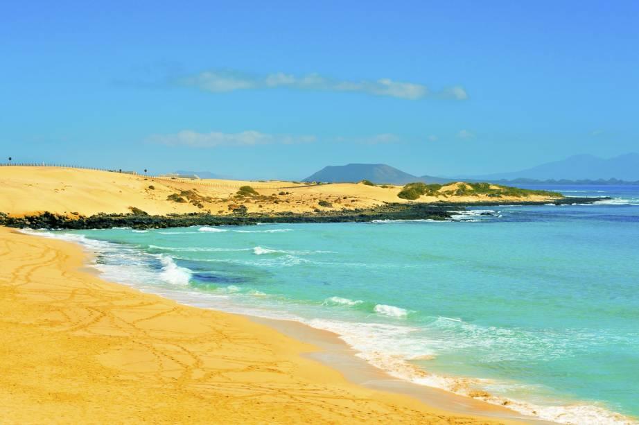 """<strong>Fuerteventura, Ilhas Canárias, <a href=""""http://viajeaqui.abril.com.br/paises/espanha"""" rel=""""Espanha"""" target=""""_self"""">Espanha</a></strong>                """"Ilha da tranquilidade"""": é assim que muitos conhecem Furteventura, marcada por praias tranquilas em meio a cenários rurais. Localizadas em uma região vulcânica, muitas de suas praias podem apresentar areia mais escura. Um dos grandes destaques são as <strong>Dunas de Corralejo</strong>, localizadas em uma área de preservação ambiental e acopladas a um parque natural de rara beleza                <em><a href=""""http://www.booking.com/region/es/canary-islands.pt-br.html?sid=5b28d827ef00573fdd3b49a282e323ef;dcid=1/?aid=332455&label=viagemabril-as-mais-belas-praias-do-mediterraneo"""" rel=""""Veja preços de hotéis próximos a Fuerteventura no Booking.com"""" target=""""_blank"""">Veja preços de hotéis próximos a Fuerteventura no Booking.com</a></em>"""