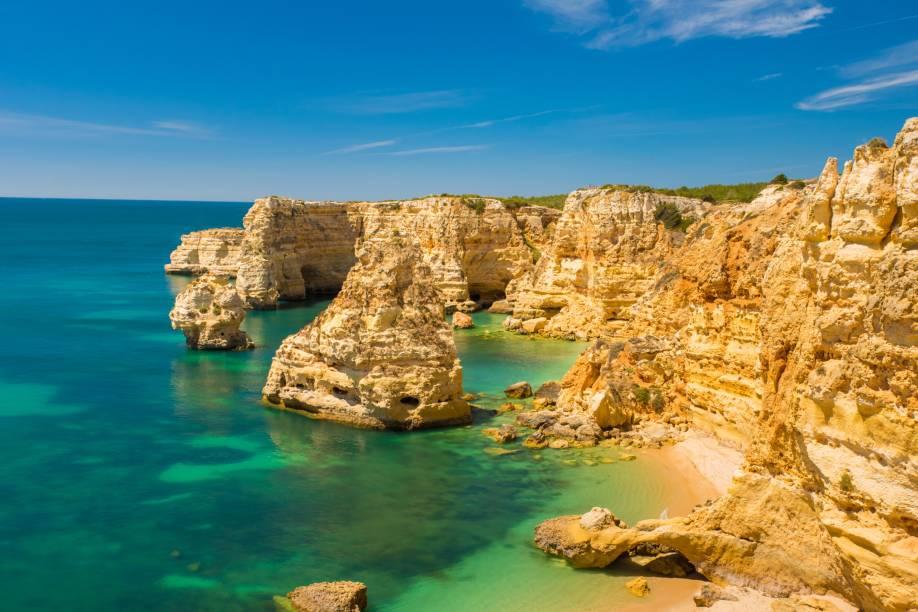 """<strong>Praia da Marinha, Algarve, <a href=""""http://viajeaqui.abril.com.br/paises/portugal"""" rel=""""Portugal"""" target=""""_self"""">Portugal</a></strong>                O título não é brincadeira: é uma das mais belas e emblemáticas praias do país, além de já ter sido eleita pelo Guia Michelin como uma das cem praias mais bonitas do mundo. Sua encosta é formada por falésias, marcando a beleza de águas cristalinas perfeitas para mergulho. Seu acesso é feito por uma escadaria, de onde se pode observar a vegetação de tomilhos silvestres                <em><a href=""""http://www.booking.com/city/pt/carvoeiro.pt-br.html?sid=5b28d827ef00573fdd3b49a282e323ef;dcid=1?aid=332455&label=viagemabril-as-mais-belas-praias-do-mediterraneo"""" rel=""""Veja preços de hotéis próximos à Praia da Marinha no Booking.com"""" target=""""_blank"""">Veja preços de hotéis próximos à Praia da Marinha no Booking.com</a></em>"""