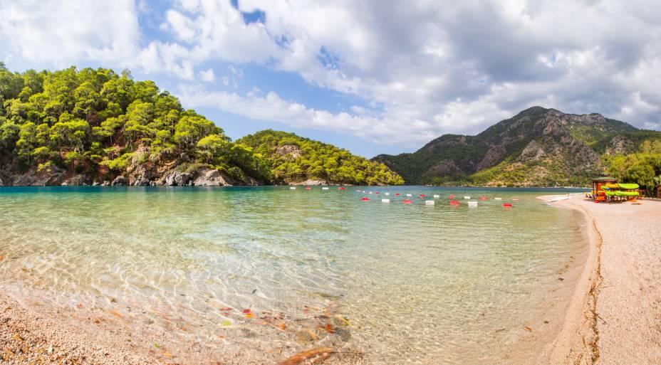 """<strong>Oludeniz, Fethiye, <a href=""""http://viajeaqui.abril.com.br/paises/turquia"""" rel=""""Turquia"""" target=""""_self"""">Turquia</a></strong>                A beleza do lugar é fascinante – tanto que ele já figurou na lista de praias mais lindas do mundo. O cenário da Montanha Babadag, que marca seu entorno, atrai inúmeros praticantes de parapente, que observam a linda paisagem litorânea que a cerca                <em><a href=""""http://www.booking.com/city/tr/oludeniz.pt-br.html?sid=5b28d827ef00573fdd3b49a282e323ef;dcid=1?aid=332455&label=viagemabril-as-mais-belas-praias-do-mediterraneo"""" rel=""""Veja preços de hotéis em Oludeniz no Booking.com"""" target=""""_blank"""">Veja preços de hotéis em Oludeniz no Booking.com</a></em>"""