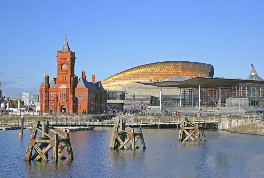 """Uma das clássicas vistas da cidade de <strong>Cardiff</strong> é deste edifício de paredes vermelhas, no porto – construído inicialmente para atender as demandas portuárias, em 1897, hoje o prédio, apelidado carinhosamente de """"Baby Big Ben"""", é um museu. Ao fundo, é possível ver o modernoso Millenium Stadium, outro símbolo local"""