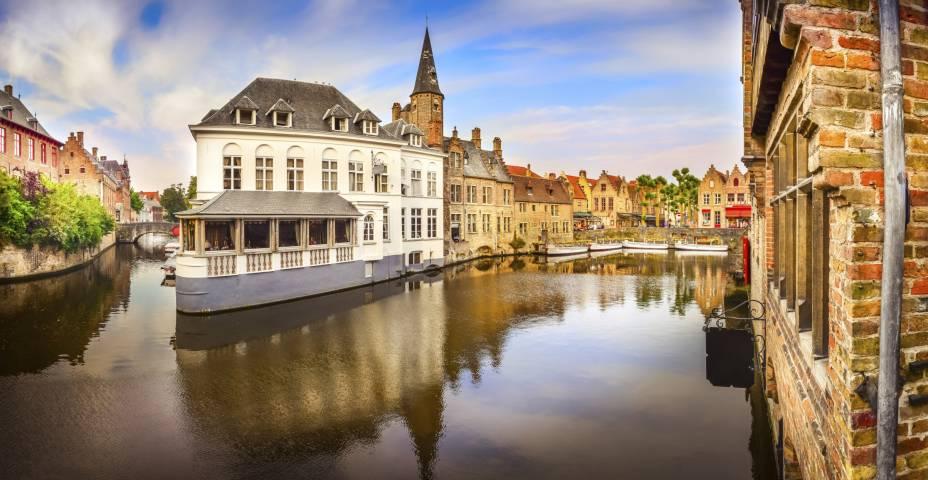 """<a href=""""http://viajeaqui.abril.com.br/cidades/belgica-bruges"""" rel=""""Bruges"""" target=""""_blank"""">Bruges</a>, com seus canais que envolvem os edifícios históricos, é carinhosamente chamada de """"Veneza do Norte"""""""