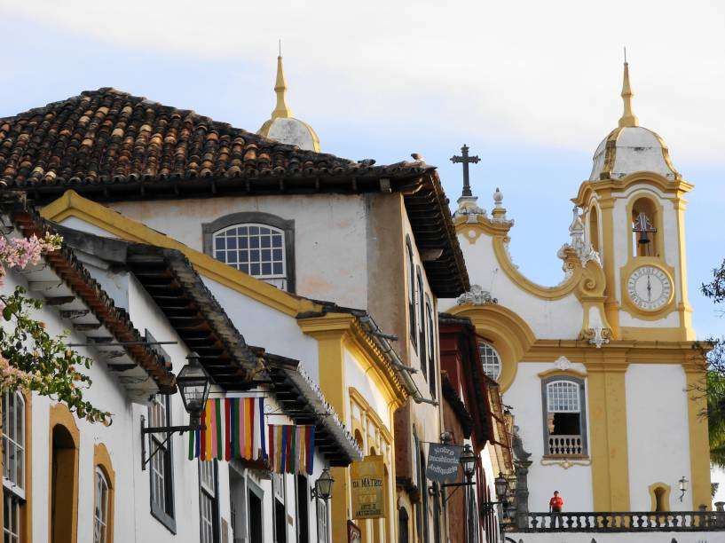 """<strong>Tiradentes (MG)</strong><a href=""""http://viajeaqui.abril.com.br/cidades/br-mg-tiradentes""""><strong> </strong></a> Uma das cidades históricas mais bem preservadas do Brasil, conserva até hoje seus ares de interior. Tiradentes tem proporções bem mais modestas que Ouro Preto, excelentes cachoeiras ao redor, gastronomia de primeira qualidade (sete restaurantes premiados pelo Guia Brasil 2015) e um bônus: ainda que esteja na Serra de São José, tem pouquíssimas ladeiras íngremes. Inúmeros ateliês de artistas que trabalham com madeira, estanho, ferro e pedra sabão vendem suas obras nas lojinhas da cidade – e, a pouco menos de uma hora de distância, está Bichinho, uma simpática vila de artesãos. De Tiradentes, sai uma Maria Fumaça turística até São João Del Rey, cidade histórica maior e mais movimentada, um passeio que já vale a pena pela bela paisagem do caminho. Passeios de charrete e a cavalo levam até Bichinho e a outras trilhas pelas montanhas ao redor. <a href=""""https://www.booking.com/searchresults.pt-br.html?aid=332455&sid=605c56653290b80351df808102ac423d&sb=1&src=index&src_elem=sb&error_url=https%3A%2F%2Fwww.booking.com%2Findex.pt-br.html%3Faid%3D332455%3Bsid%3D605c56653290b80351df808102ac423d%3Bsb_price_type%3Dtotal%26%3B&ss=Tiradentes%2C+Minas+Gerais%2C+Brasil&checkin_monthday=&checkin_month=&checkin_year=&checkout_monthday=&checkout_month=&checkout_year=&no_rooms=1&group_adults=2&group_children=0&b_h4u_keep_filters=&from_sf=1&ss_raw=Tiradentes&ac_position=0&ac_langcode=xb&dest_id=-676172&dest_type=city&place_id_lat=-21.111294&place_id_lon=-44.168297&search_pageview_id=49df83ff14c50046&search_selected=true&search_pageview_id=49df83ff14c50046&ac_suggestion_list_length=5&ac_suggestion_theme_list_length=0"""" target=""""_blank"""" rel=""""noopener""""><em>Busque hospedagens em Tiradentes</em></a>"""