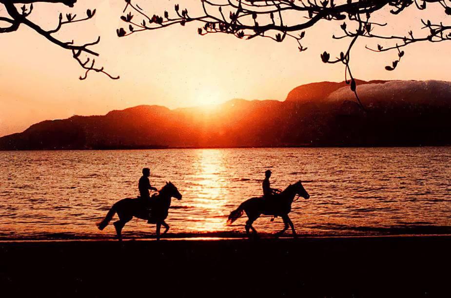 Turistas cavalgam na praia do Perequê, em Ilhabela