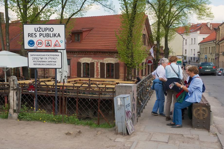 """Turistas na entrada de Uzupis, que em sua constituição diz que """"todo mundo tem o direito de ser feliz"""" e também que """"todo mundo também tem o direito de ser infeliz"""""""