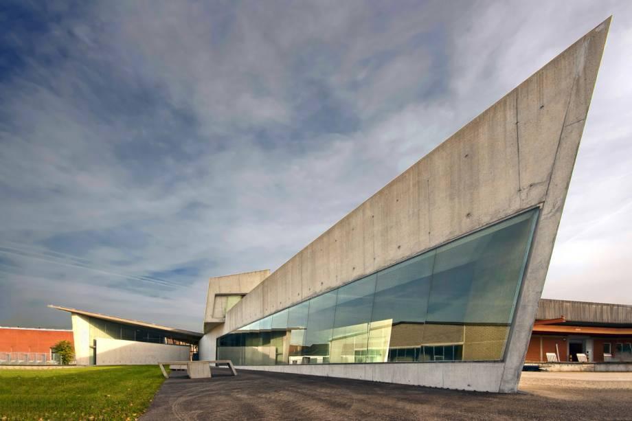 """No campus do <a href=""""https://www.vitra.com/en-cz/magazine/details/181584"""" rel=""""Vitra, """" target=""""_blank"""">Vitra, </a>um dos institutos de design mais famosos do mundo, localizado na Alemanha, quase fronteira com a Suíça, Zaha projetou o prédio do corpo de bombeiros"""