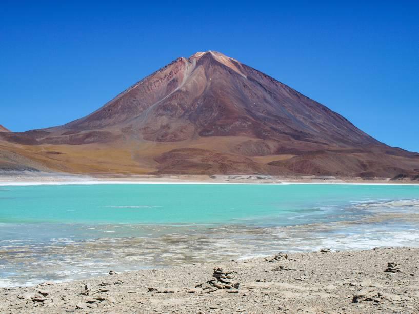 """<a href=""""http://viajeaqui.abril.com.br/paises/bolivia"""" target=""""_blank"""" rel=""""noopener""""><strong>Licancabur, Bolívia</strong></a> Localizado a 40km de <a href=""""http://viajeaqui.abril.com.br/cidades/chile-san-pedro-de-atacama"""" target=""""_blank"""" rel=""""noopener"""">San Pedro de Atacama no Chile</a>, está na fronteira entre os dois países. É ali que está o lago mais alto do mundo, dentro de seu cume de 5.913 metros de altitude. O lago tem apenas 90 x 70 metros e suas águas são mantidas a aproximadamente 6 graus, quentinho para tal altitude, graças a aquecimento geotermal que vem de dentro da terra."""