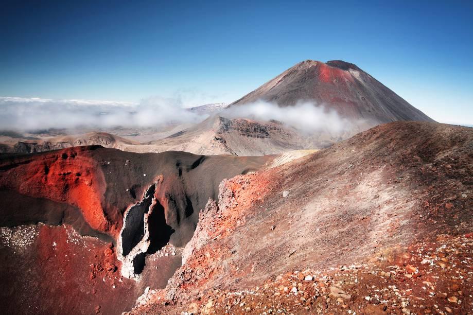 """<a href=""""http:// http://viajeaqui.abril.com.br/paises/nova-zelandia"""" target=""""_blank"""" rel=""""noopener""""><strong>Tongariro, Nova Zelândia</strong></a> Este belo vulcão é um dos três ativos da ilha norte da Nova Zelândia. Com 1.978m de altitude em seu cume mais alto, é composto por um maciço com pelo menos 12 cones. O nome deriva das palavras maori """"tonga"""" (vento sul) e """"riro"""" (arribado, aportado), que veio de uma lenda. Senta que lá vem história: <em>Segundo a lenda, o grande navegador Ngatoroirangi, padre da migração Arawa no século XIV, escalou o Tongariro e, chegando lá em cima, enquanto ele perecia no cume da grande montanha e esperando que os deuses lhe enviassem fogo, ele disse """"Ka riro au I te tonga"""" (Eu estou aportado no amargo vento sul)</em>."""