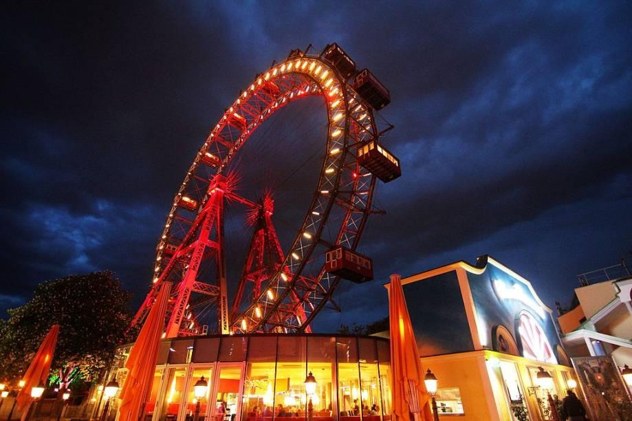 """Wiener Riesenrad significa literalmente """"roda-gigante vienense"""". Foi construída em 1897 no parque de diversões Wurstelprater de <a href=""""http://viajeaqui.abril.com.br/cidades/austria-viena"""" target=""""_self"""">Viena</a>, na Áustria, e por mais de 60 anos levou o título de maior do mundo. Hoje não parece tão imponente, nem chega a 65 metros de altura, mas é uma sobrevivente: em 1916 autorizaram a sua demolição, mas faltaram fundos para fazer o serviço e decidiram mantê-la ali, sem incomodar ninguém. Com a chegada da Segunda Guerra Mundial, sofreu danos – das 30 gôndolas originais, só sobraram 15. Mas continua como sempre, firme e forte, sendo um dos principais atrativos turísticos da região"""