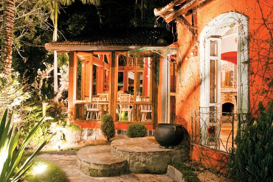 """O centro de Penedo encanta casais e famílias com suas lojas de chocolate e construções de madeira com telhados triangulares; na foto, o ambiente do <a href=""""http://viajeaqui.abril.com.br/estabelecimentos/br-rj-penedo-restaurante-jardim-secreto"""" rel=""""restaurante Jardim Secreto"""" target=""""_blank"""">restaurante Jardim Secreto</a>"""