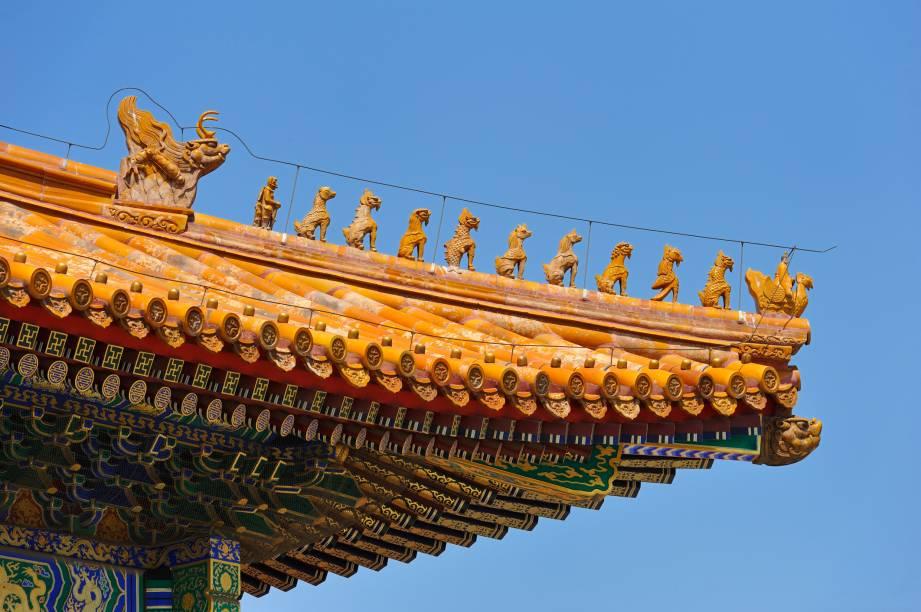 Motivos decorativos em telhado na Cidade Proibida, Pequim, China. Esse tipo de decoração só era realizado em edifícios imperiais, sendo que aqui a procissão de imagens é liderada por um fênix.