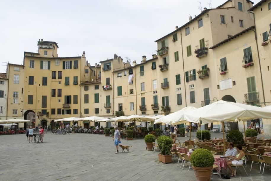A forma ovalada da Piazza Anfiteatro, em Lucca, é emoldurada por antigos prédios de fachadas em tons pastéis e agradáveis cafés