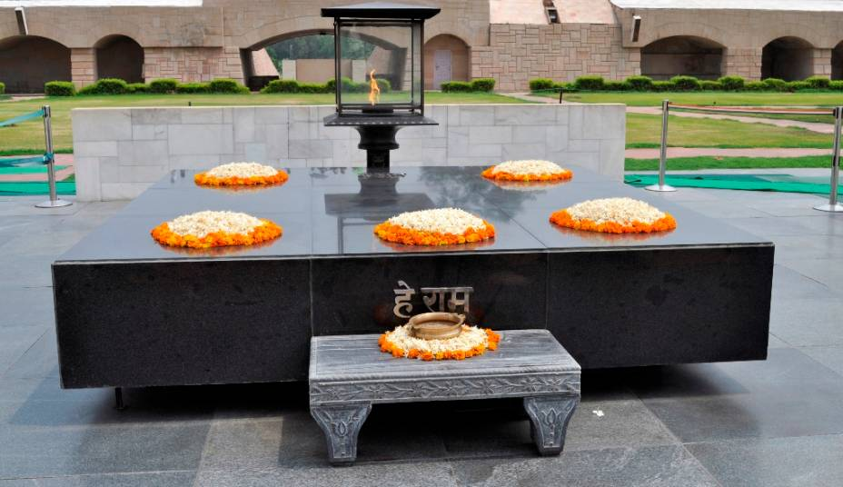 """Raja Ghat, um memorial a Mahatma Gandhi, em Nova Délhi, é um local popular de visita entre turistas estrangeiros e indianos. A inscrição em hindi são as últimas palavras de Gandhi: """"oh, Deus!"""""""