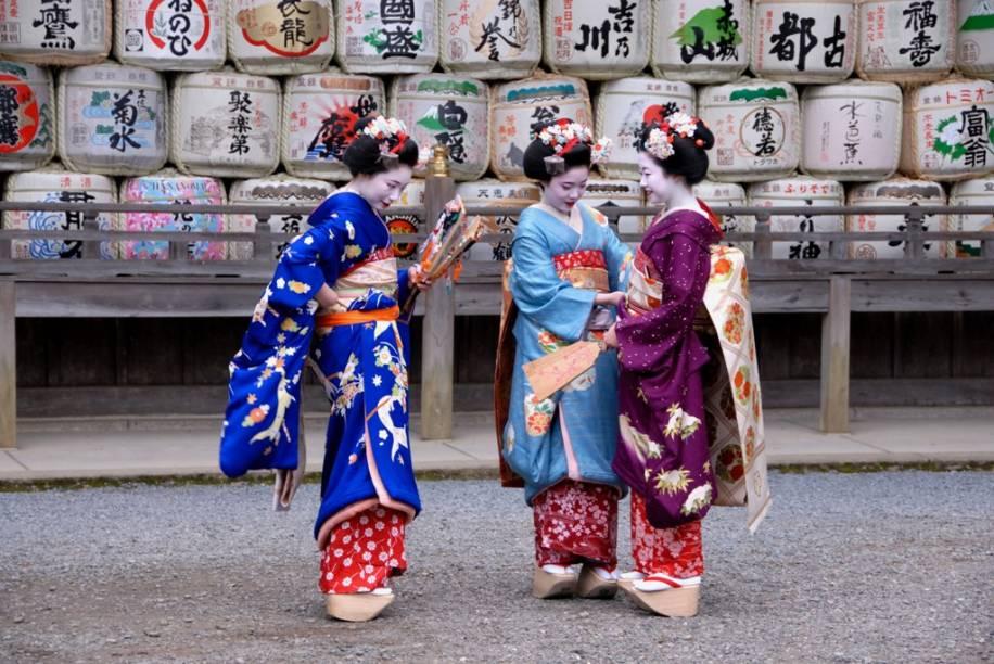 Aprendizes de geisha, conhecidas como maiko, vestem-se com seus coloridos kimonos no santuário Matsuo Taisha, em Kyoto. Ao fundo, tambores de sakê utilizados como oferendas.