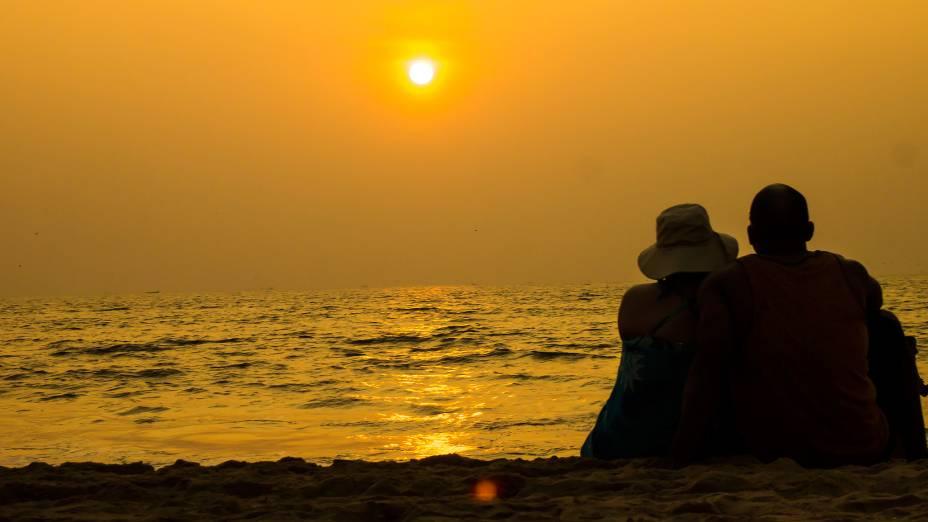 Casal assiste ao pôr do sol em praia de Goa, na Índia