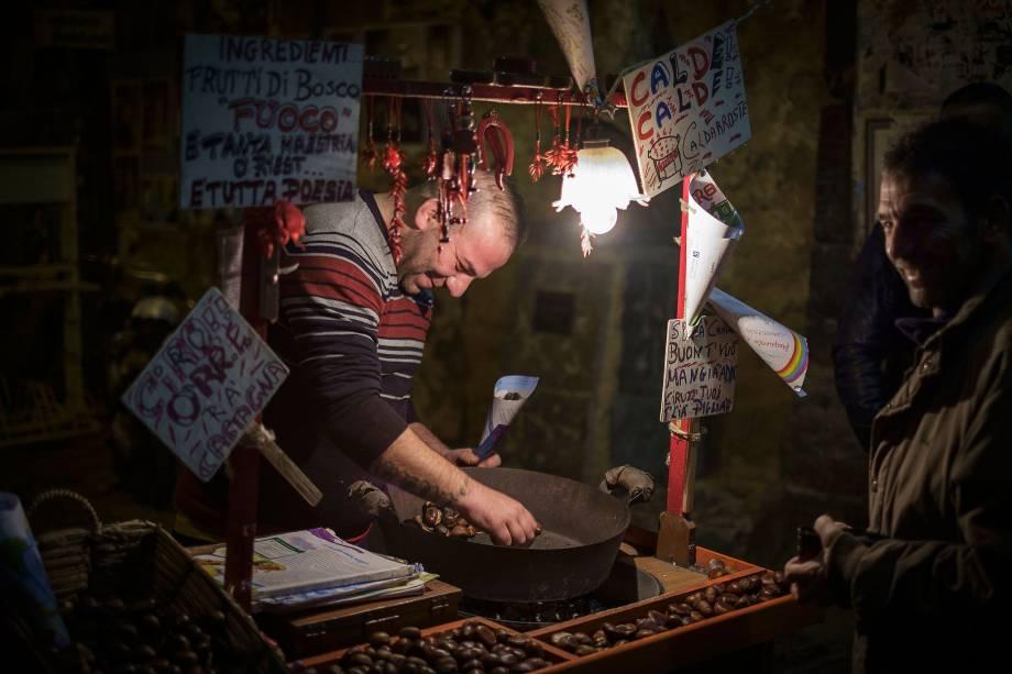 Vendedor de rua torra castanhas para clientes na noite de Nápoles, Itália - é fácil sentir o cheiro de castanhas açucaradas e torradas pela cidade