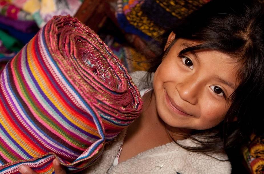 Garota prepara tecidos em fábrica de Chichicastenango, Guatemala