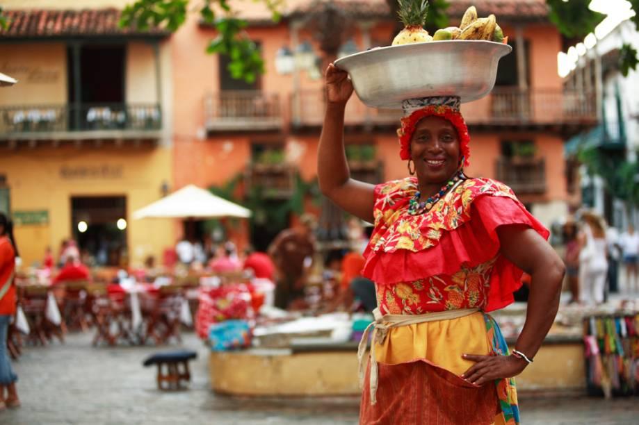 As vendedoras de frutas, chamadas de palenqueras, percorrem as ruas da cidade com seus vestidos coloridos e bacias na cabeça