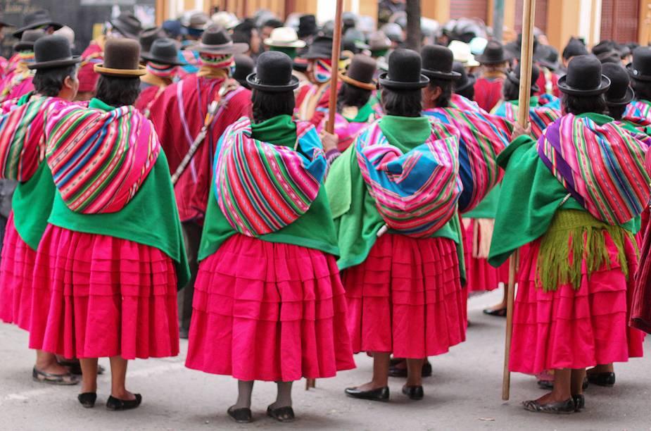 Mulheres indígenas reúnem-se em protesto nas ruas de La Paz, Bolívia. Cada região do país tem o seu povo indígena, e cada povo tem os seus hábitos de vestimenta. Na capital, por exemplo, as mulheres costumam usar saias muito brilhantes e cores vivas e chapéus pretos no topo da cabeça. No interior, o chapéu dá lugar a longas e trabalhadas tranças